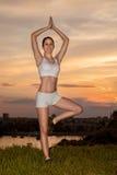 Allungamento della giovane donna all'aperto nel tramonto Fotografie Stock Libere da Diritti