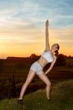Allungamento della giovane donna all'aperto nel tramonto Immagini Stock