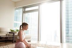 Allungamento della giovane donna, facente esercizio di yoga con il computer portatile a casa Immagini Stock