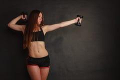 Allungamento della giovane donna nelle teste di legno di uso degli abiti sportivi Immagine Stock Libera da Diritti