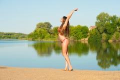 Allungamento della ragazza in bikini sul fondo del lago Fotografia Stock