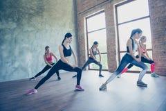 Allungamento delle signore dei muscoli delle anche Cinque giovani sportive esili sono Fotografia Stock