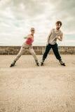 Allungamento di esercizio di due genti all'aperto sui rollerblades Fotografie Stock