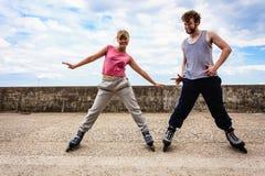 Allungamento di esercizio di due genti all'aperto sui rollerblades Fotografia Stock Libera da Diritti