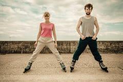 Allungamento di esercizio di due genti all'aperto sui rollerblades Fotografie Stock Libere da Diritti