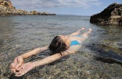 Allungamento di galleggiamento della ragazza sulla spiaggia Immagini Stock Libere da Diritti
