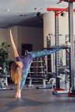 Allungamento di modello di forma fisica femminile in un club della palestra Immagine Stock