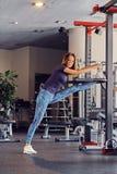 Allungamento di modello di forma fisica femminile in un club della palestra Fotografie Stock Libere da Diritti