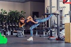 Allungamento di modello di forma fisica femminile in un club della palestra Fotografia Stock