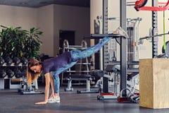 Allungamento di modello di forma fisica femminile in un club della palestra Immagine Stock Libera da Diritti