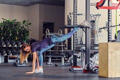 Allungamento di modello di forma fisica femminile in un club della palestra Immagini Stock