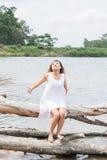 Allungamento di seduta della giovane donna le sue mani sul tronco di albero nel lago e Fotografie Stock
