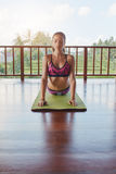 Allungamento facente femminile del centro di forma fisica sulla stuoia di yoga Fotografie Stock