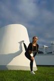 Allungamento felice della ragazza all'aperto ad area urbana moderna durante il tramonto Fotografia Stock