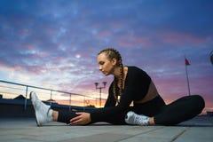 Allungamento felice della ragazza all'aperto ad area urbana moderna durante il tramonto Fotografia Stock Libera da Diritti