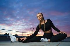 Allungamento felice della ragazza all'aperto ad area urbana moderna durante il tramonto Immagine Stock
