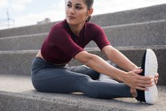 Allungamento femminile abbastanza giovane sulle scale Fotografia Stock