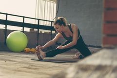 Allungamento femminile dell'atleta Fotografie Stock
