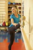 Allungamento femminile nella classe variopinta di forma fisica con il corrimano Fotografia Stock