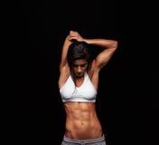 Allungamento femminile sportivo prima del suo allenamento Fotografia Stock
