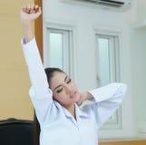 Allungamento femminile stanco di medico Immagine Stock