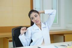 Allungamento femminile stanco di medico Fotografia Stock Libera da Diritti
