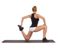 Allungamento femminile sull'esercizio Mat Before Workout Fotografie Stock