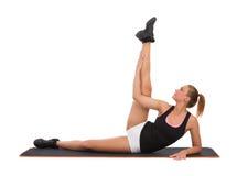 Allungamento femminile sull'esercizio Mat Before Workout Immagini Stock Libere da Diritti