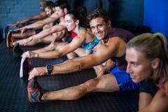 Allungamento giovane degli amici dell'atleta Fotografie Stock Libere da Diritti
