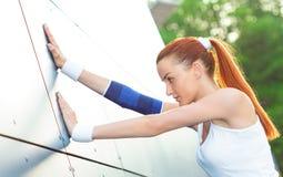 Allungamento scaldarsi femminile dell'atleta Immagini Stock