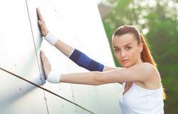 Allungamento scaldarsi femminile dell'atleta Immagini Stock Libere da Diritti
