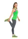 Allungamento sorridente della giovane donna di forma fisica Fotografie Stock Libere da Diritti