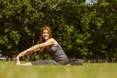 Allungamento sorridente della testarossa graziosa nel parco Immagine Stock Libera da Diritti