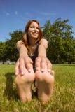 Allungamento sorridente della testarossa graziosa nel parco Fotografia Stock Libera da Diritti