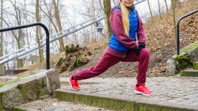Allungamento sportivo della ragazza all'aperto in parco Immagine Stock