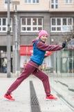 Allungamento sportivo della ragazza all'aperto sulla via della città Fotografie Stock