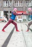 Allungamento sportivo della ragazza all'aperto sulla via della città Immagini Stock Libere da Diritti