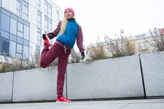 Allungamento sportivo della ragazza all'aperto sulla via della città Fotografia Stock