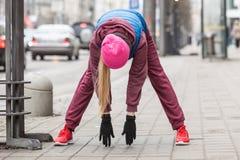 Allungamento sportivo della ragazza all'aperto sulla via della città Fotografia Stock Libera da Diritti