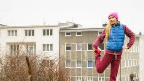 Allungamento sportivo della ragazza all'aperto sulla via della città Immagini Stock