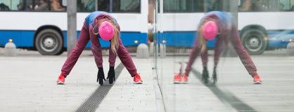 Allungamento sportivo della ragazza all'aperto sulla via della città Fotografie Stock Libere da Diritti