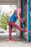 Allungamento sportivo della ragazza all'aperto sulla via della città Immagine Stock
