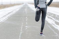 Allungando correre - corridore della donna che fa gli esercizi Marath di inverno Immagine Stock Libera da Diritti