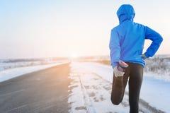 Allungando correre - corridore della donna che fa gli esercizi Marath di inverno Fotografia Stock