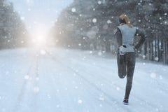 Allungando correre - corridore della donna che fa gli esercizi Marath di inverno Immagini Stock Libere da Diritti