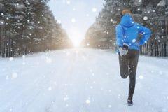 Allungando correre - corridore della donna che fa gli esercizi Marath di inverno Fotografie Stock Libere da Diritti