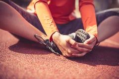 Allungando dopo l'allenamento Chiuda sull'immagine delle gambe della donna Fotografie Stock Libere da Diritti