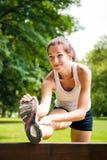 Allungando esercitazione - donna di sport esterna Fotografie Stock