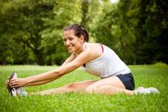 Allungando esercitazione - donna di sport esterna Fotografia Stock