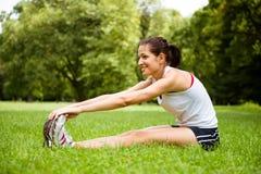 Allungando esercitazione - donna di sport esterna Fotografie Stock Libere da Diritti